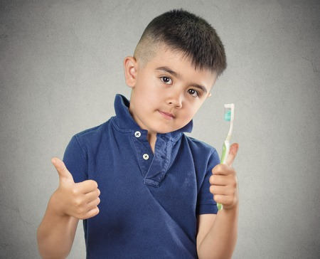 Closeup portrait happy boy brushing his teeth with toothpaste manual toothbrush showing thumbs up isolated grey wall background. Oral dental health, hygiene disease prevention. Face expressions.  photo
