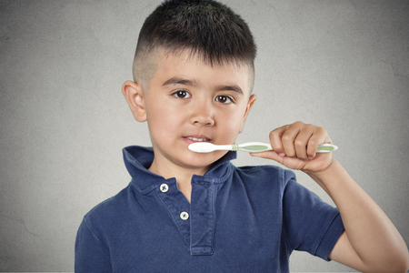 Closeup portrait happy, smiling little boy brushing his teeth with toothpaste, manual toothbrush isolated grey wall background. Oral dental health, disease prevention. Positive face expressions photo