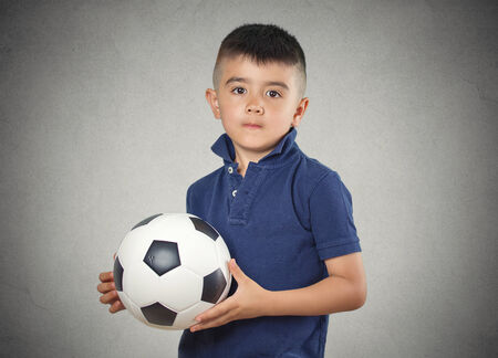 Future soccer player. Boy holding football ball isolated grey wall background. Confident face expression photo