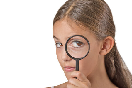 investigating: Curious. Child looking through a magnifying glass, isolated on white background. Human face expressions Stock Photo