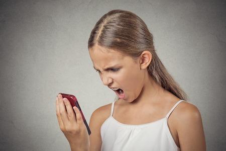 conflictos sociales: Primer retrato joven enojado, frustrado chica adolescente enojado gritando mientras que en el tel�fono aislado fondo de la pared gris. Negativos emoci�n humana sentimientos de expresi�n facial. La comunicaci�n, la resoluci�n de conflictos