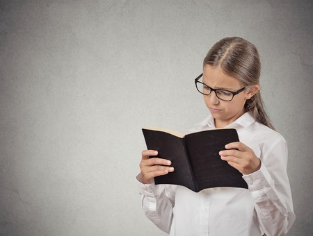 closeup portrait child with glasses reading book, isolated grey wall background. Face expressions. Education concept