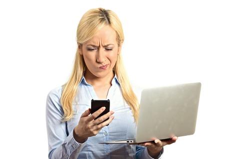 business skeptical: Retrato del primer noticias sorprendido esc�pticos mujer de negocios corporativo lectura en el tel�fono m�vil inteligente celebraci�n de ordenador port�til aislado fondo blanco. Expresi�n del rostro humano emoci�n, el lenguaje corporal Foto de archivo