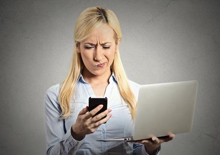 business skeptical: Retrato del primer de noticias sorprendido esc�pticos mujer de negocios corporativo lectura en el tel�fono m�vil inteligente ordenador port�til holding gris pared de fondo negro. Emoci�n expresi�n humana de ejecutivo Foto de archivo