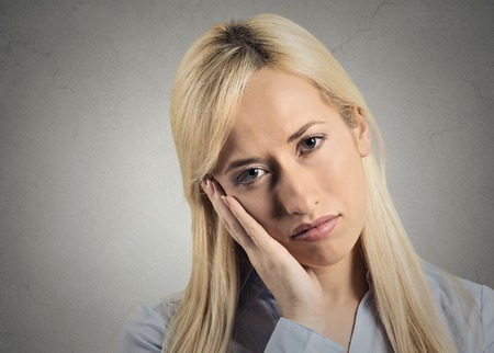 bothered: Depressed gloomy. Closeup portrait unhappy young woman head on hand bothered by mistake situation having bad headache isolated grey wall background. Negative human emotion facial expression feeling