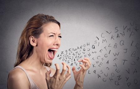Vue latérale portrait femme en colère criant, lettres de l'alphabet qui sortent de la bouche ouverte, mur gris fond isolé. Expressions négatives humaines pour le visage, l'émotion, la réaction. Conflit, le concept de confrontation Banque d'images