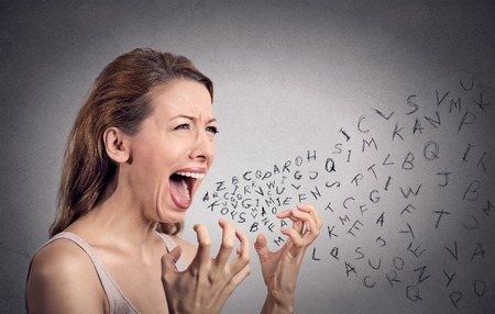 Side view portrait angry woman screaming, alphabet letters coming out of open mouth, isolated grey wall background. Negative human face expressions, emotion, reaction. Conflict, confrontation concept Stockfoto