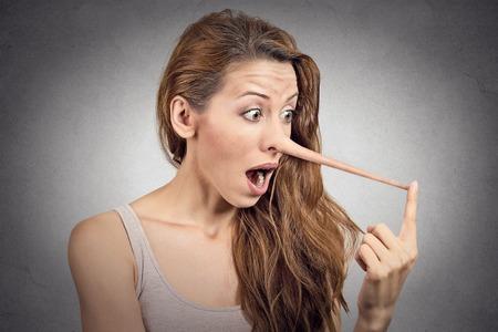 nariz: Mujer con la nariz larga aislada en el fondo de la pared gris. Concepto Liar. Expresiones faciales humanas, emociones, sentimientos. Foto de archivo