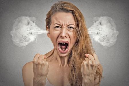 クローズ アップ肖像怒っている若い女性の耳から出てくる蒸気を吹いて神経原子破壊を叫ぶことは灰色の壁の背景を隔離しました。否定的な人間の 写真素材