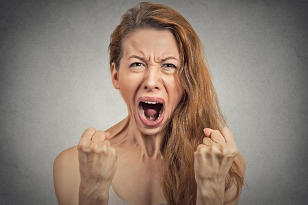 Closeup portrait angry young woman hysterical having nervous atomic breakdown, screaming, fists up in air isolated grey wall background. Negative human emotion facial expression feeling bad attitude