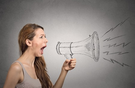 loud speaker: Angry screaming woman holding megaphone isolated on grey wall background. Negative face expressions, emotions, feelings. Propaganda, breaking news, power, social media concept