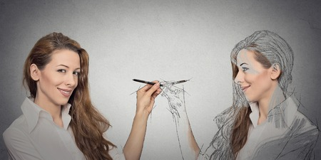 mirror: Create yourself, your future destiny, image, career concept. Attractive young woman drawing a picture, sketch of herself on grey wall background. Human face expressions, determination, creativity