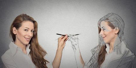 espejo: Cree usted mismo, su destino futuro, la imagen, el concepto de carrera. Atractiva mujer joven haciendo un dibujo, boceto de s� misma en el fondo gris de la pared. Expresiones faciales humanos, la determinaci�n, la creatividad Foto de archivo