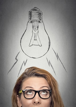 intuition: Headshot thinking businesswoman with glasses having an idea looking up with light bulb over her head isolated grey wall background. Human face expressions, emotions. Creativity concept