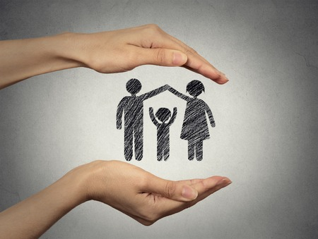 notion: close up of womans hands protecting happy family, mother, father, child. Family abstract in palms on grey wall background. Safe childhood, parenting. Love care compassion safety secure future concept