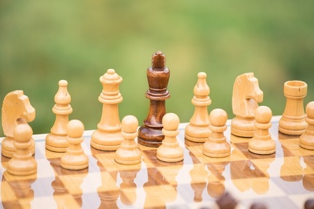 Closeup wooden chess figures with black king surrounded by white army on chessboard. Lost leader, politics, negotiation, strategy, power, tactic concept