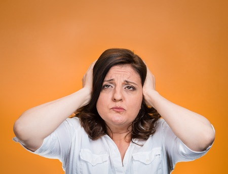 unpleasant: Closeup portrait middle aged annoyed unhappy stressed woman covering ears looking up stop making loud noise giving me headache isolated orange background. Negative emotion, reaction, face expression