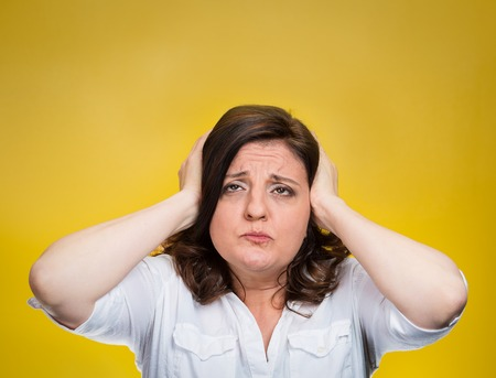 decibel: Closeup portrait middle aged annoyed unhappy stressed woman covering ears looking up stop making loud noise giving me headache isolated yellow background. Negative emotion, reaction, face expression