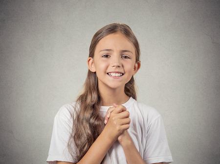 solicit: Closeup portrait teenager girl gesturing with clasped hands, pretty please with sugar on top, isolated grey wall background. Human emotions, facial expressions, feelings, signs symbols, body language