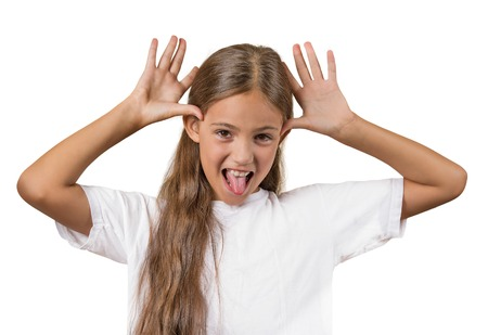 attitude girls: Portrait young funny teenager girl sticking out tongue at you camera gesture, thumbs hands on temple, mocking someone isolated white background. Human emotion, facial expression, feeling attitude