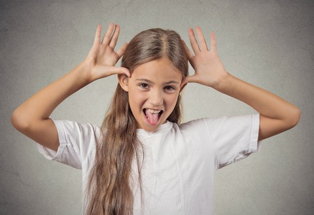 rebellious: Portrait young funny teenager girl sticking out tongue at you camera gesture, thumbs hands on temple, mocking someone isolated grey wall background. Human emotion, facial expression, feeling attitude Stock Photo