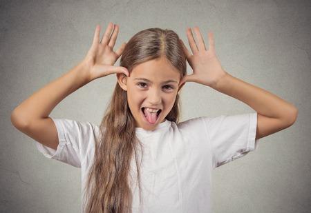 sacar la lengua: Retrato joven chica adolescente lindo que se pega hacia fuera la lengua en su c�mara gesto, pulgares manos en el templo, burl�ndose de alguien aislado fondo de la pared gris. La emoci�n humana, la expresi�n facial, la actitud de sentimiento