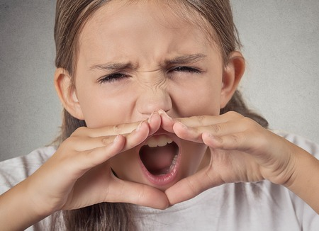 Closeup portrait, headshot angry, upset, hostile, furious teenager girl yelling, screaming, hands to mouth isolated grey wall background. Negative human emotions, facial expression reaction attitude Stock Photo