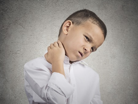 Neck pain. Portrait stressed unhappy child boy with back pain, after long school hours studying isolated grey wall background. Negative human emotions facial expression feeling. Wrong position at desk