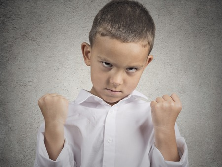 simulations: Closeup portrait angry child boy with fist up in air, pissed off looking grumpy isolated grey wall background. Negative human Emotions Facial Expression body language attitude perception confrontation Stock Photo