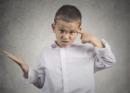 クローズ アップ肖像怒り狂った子少年狂気であるを求めて寺に対して彼の指でジェスチャーですか。灰色の壁背景を分離しました。人間の負の感情