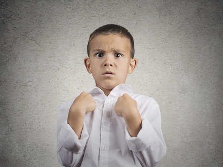lack of confidence: Closeup portrait surprised child boy getting unexpected attention from people asking you talking to, mean me? pointing fingers at himself isolated grey wall background. Human facial expression emotion