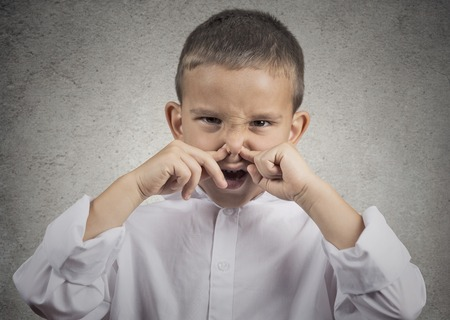stinks: Closeup portrait child boy with disgust on face pinches his nose something stinks bad smell situation isolated grey wall background. Negative human emotions facial expressions perception body language