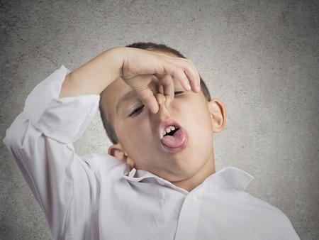 percepci�n: Retrato del primer ni�o ni�o con disgusto en la cara pellizca la nariz algo apesta situaci�n olor mal aislado fondo de la pared gris. Emociones humanas negativas expresiones faciales lenguaje corporal percepci�n Foto de archivo