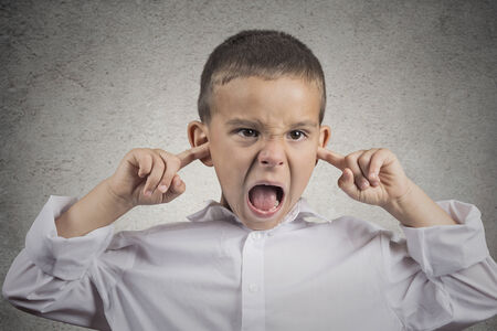 disobedient child: Closeup portrait angry annoyed pissed off boy plugs his ears with fingers sticking out tongue looking with funny negative facial expression, disapproval isolated grey wall background. Human emotions Stock Photo
