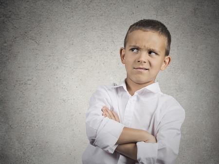 gezichts uitdrukkingen: Close-up portret headshot verdachte, voorzichtige kind jongen opzoeken met ongeloof, geïsoleerd scepsis grijze muur achtergrond. Menselijke gezichtsuitdrukkingen emoties lichaamstaal perceptie houding