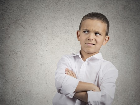 Closeup up portrait headshot suspicious, cautious child boy looking up with disbelief, skepticism isolated grey wall background. Human facial expressions emotions body language perception attitude