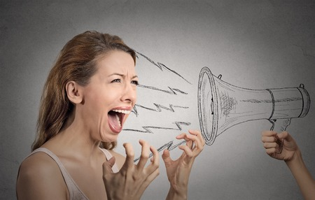 Portrait angry hysterical woman shouting against someones loud megaphone isolated grey wall background. Negative human face expressions, emotions, feelings. Lack of emotional intelligence concept Stock Photo