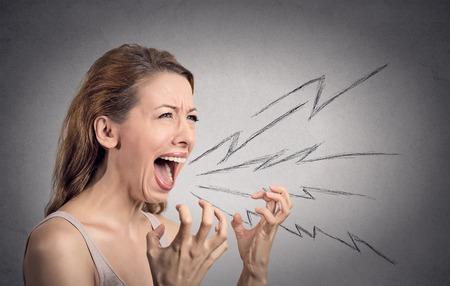 Vue latérale portrait femme en colère cris, bouche grande ouverte, hystérique isolé gris mur arrière-plan. Expressions négatives humaines pour le visage, l'émotion, mauvaise réaction des sentiments. Conflit, le concept de confrontation Banque d'images
