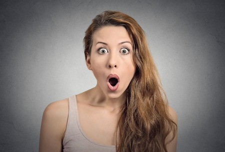 woman mouth open: Surprise astonished woman. Closeup portrait woman looking surprised in full disbelief  wide open mouth isolated grey wall background. Positive human emotion facial expression body language. Funny girl Stock Photo