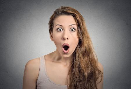Surprise femme étonnée. Gros plan femme portrait air surpris en pleine incrédulité bouche grande ouverte mur gris isolé fond. Émotion humaine expression faciale langage corporel positif. Funny girl