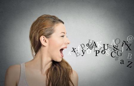 languages: Vista lateral retrato de la mujer que habla con las letras del alfabeto que sale de su boca abierta aislado fondo de la pared gris. Expresiones faciales humanas, emociones. Comunicación, información, concepto de inteligencia