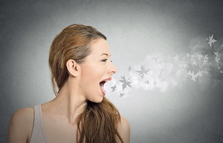 chewing gum: side profile portrait headshot of beautiful girl with leaves flying from her open mouth isolated grey wall background. Human face expressions, emotions. Autumn, winter season, cold weather concept