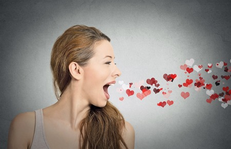coming out: Side view portrait beautiful woman sending kisses, red hearts coming out of open mouth, isolated grey wall background. Positive emotions, facial expression, feelings, life perception. valentines day