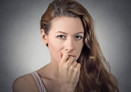 deciding: portrait of worried woman thinking looking at you camera isolated grey wall background. human face expressions, emotions, feelings Stock Photo