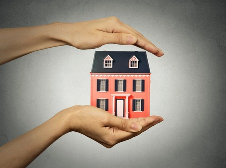home protection: Portrait woman hands presenting small model of house, isolated grey wall background. Real estate, mortgage, home ownership concept. Safety, strong family idea. Insurance, protection