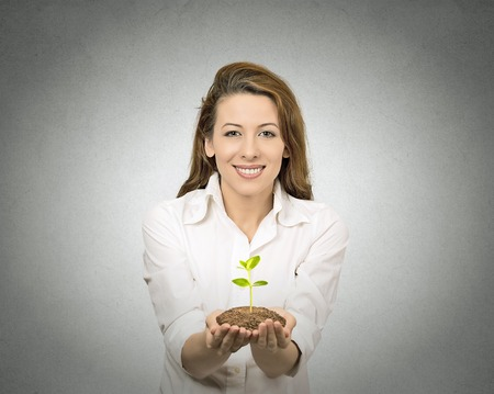 closeup one plant in female hands isolated grey wall background. Positive human face expressions, emotions. Green earth, planet care, nature, agriculture, ecology concept, perception, attitude photo