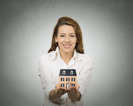 Portrait happy smiling  woman presenting small model of house, isolated grey wall background. Positive human face expressions, emotions, feelings. Real estate, home ownership concept photo
