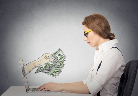 coming out: business woman with glasses working online on computer making earning money, hand with dollar bills banknotes coming out of laptop screen, isolated grey wall office background. Human face expression