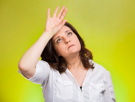 woe: Closeup portrait annoyed tired middle aged woman placing back hand on forehead, tragedy of it all, woe is me, exaggerating isolated green background. Negative emotion, facial expression, perception
