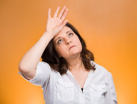 woe: Closeup portrait annoyed tired middle aged woman placing back hand on forehead, tragedy of it all, woe is me, exaggerating isolated orange background. Negative emotion, facial expression, perception